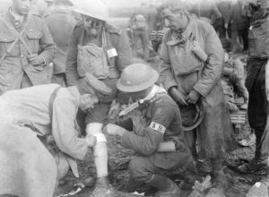 Wounded soldier receives first aid from stretcher bearer on frontline
