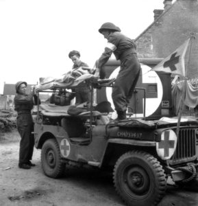 Medics load patient on jeep ambulance in Italy Source: Library and Archives Canada / PA-113872