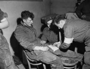 Medic checks dressing on injured soldier