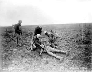 Wounded soldier receiving first aid on battlefield