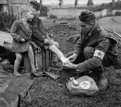 Royal Canadian Army Medical Corps (RCAMC) medic treating injured child