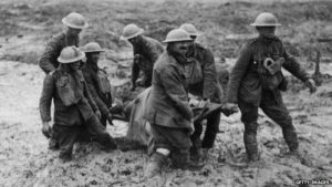 Stretcher bearers carry wounded through mud somewhere in France or Belgium