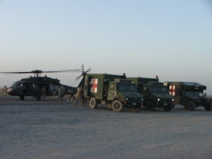 Canadian and US ambulance at Role 3 Medical Unit Afghanistan with Blackhawk Medevac helicopter in the background.