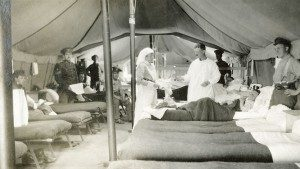 A nursing sister is assisting a doctor in a ward at the tent hospital. She is holding out a tray for him to take instruments.