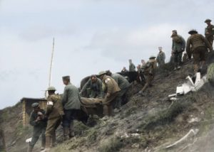 German POWs assist Canadian stretcher bearers carry casualty down difficult terrain Source: