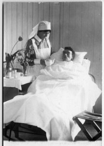 Nursing sister is preparing to assist a patient with a drink at the no. 2 Canadian General Hospital in Le Treport, France. Source: Agnes Warner and the Nursing Sisters of the Great War (Fredericton, NB: Goose Lane Editions